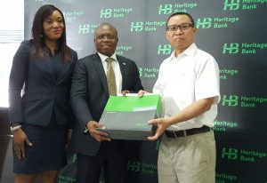 Mrs. Adaeze Udensi, Executive Director; Retail & SME Bank; Jude Monye, Executive Director Business Banking; who both represented the MD/CEO of Heritage Bank Plc, Ifie Sekibo; presenting a gift to the General Manager, Biase Plantations Limited (BPL), Mr. Ahmad Mustaffa Goh, at the signing ceremony of N232million Pilot Out-growers' Agreement between the Bank and BPL at Heritage Bank's Head Office, Lagos.