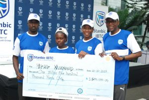 """Chief Executive, Stanbic IBTC Holdings Plc, Mr. Yinka Sanni; Non-Executive Director, Stanbic IBTC Holdings Plc, Mrs. Ngozi Edozien; a beneficiary prosthetic limbs & education trust  donated by Stanbic IBTC, Hawa Mohammed; Father of the beneficiary, Mr. Mohammed during the presentation of cheques to beneficiaries of Stanbic IBTC 2017 """"Together For A Limb"""" CSI Initiative in Lagos, on Saturday, 28 Oct, 2017"""