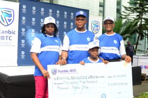 """Mother of the beneficiary, Mrs. Loveth Azuka; Representative of the Minister of Health, Prof. Chris Bode; a beneficiary prosthetic limbs & education trust donated by Stanbic IBTC, Blessing Azuka; and Chairman, Stanbic IBTC Asset Management Limited, Mrs. Ifeoma Esiri, during the presentation of cheques to beneficiaries of Stanbic IBTC 2017 """"Together For A Limb"""" CSI Initiative in Lagos, on Saturday, 28 Oct, 2017"""